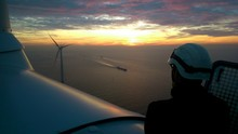 Rear View Of Technician On Wind Turbine During Sunset