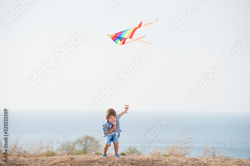 Fototapeta delightful small free active boy laughing holding flying color kite near blue sea shore and sky in summer leisure obraz