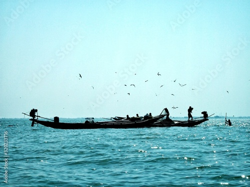 Canvas-taulu Silhouette Men On Boat In Sea Against Clear Sky