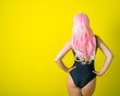 Leinwanddruck Bild - A woman with long wavy artificial hair is standing back in a black swimsuit. Fashion girl in a curly pink wig on a yellow background.