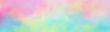 Colorful watercolor background of abstract sunset sky with puffy clouds in bright rainbow colors of pink green blue yellow and purple