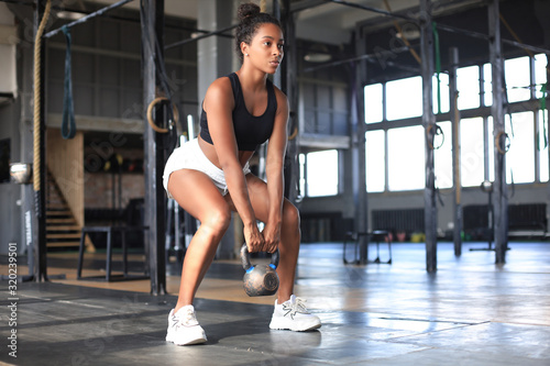 Sport woman with kettlebell in the gym. Fototapeta