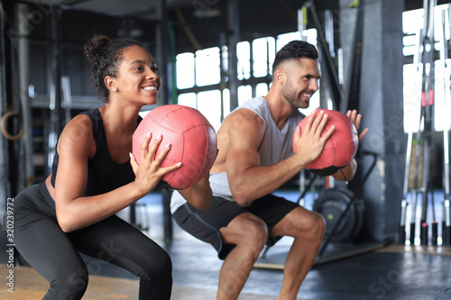 Fototapeta Beautiful young sports couple is working out with medicine ball in gym