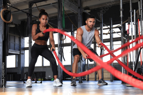 mata magnetyczna Athletic young couple with battle rope doing exercise in functional training fitness gym.