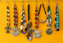 Close-Up Of Various Necklaces Hanging By Yellow Wall