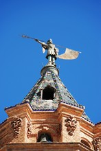 View Of The Church Bell Tower (Iglesia San Sebastian) Topped With A Statue, Antequera, Spain.