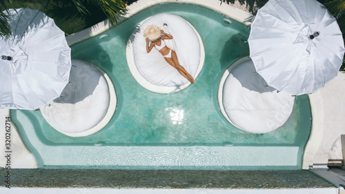 Woman relaxing in clear pool water in hot sunny day on Bali villa Wallpaper Mural