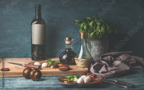 Food still life with oil bottles, mozzarella,  tomatoes and kitchen herbs in pot on kitchen table background