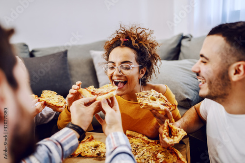 Fototapeta Group of friends sitting on the floor in living room, drinking beer and eating pizza. House party. Man feeding his girlfriend. obraz
