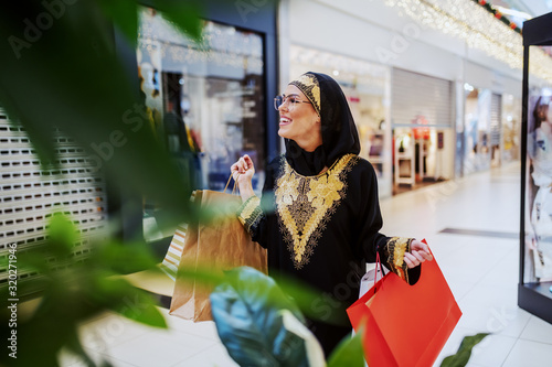 Photo Excited attractive muslim woman walking in shopping mall with shopping bags in hands and looking for another pretty dress for her