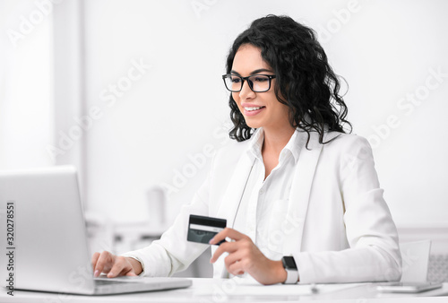 Fotografia, Obraz Happy latin girl making donations using laptop