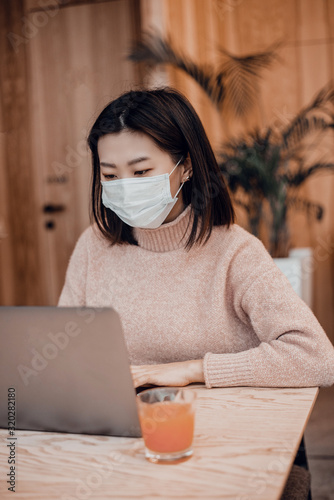 Asian woman in a protective mask sits in a cafe at a laptop Wallpaper Mural
