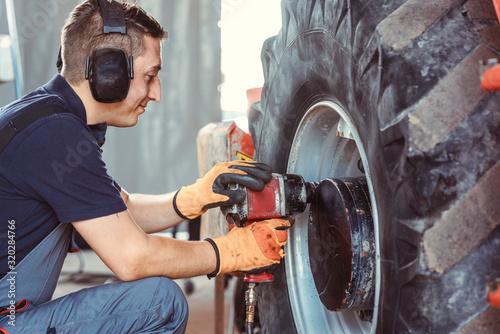 Fototapeta Farm machine mechanic working on wheel obraz