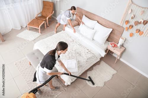 Photo Beautiful chambermaids cleaning hotel room