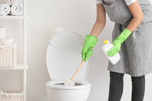 Young Woman Cleaning Toilet In...