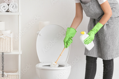 Fotografie, Obraz Young woman cleaning toilet in bathroom