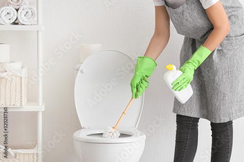 Cuadros en Lienzo Young woman cleaning toilet in bathroom