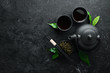 Chinese green tea in a cup with a kettle. On a black stone background. Top view. free space for your text.