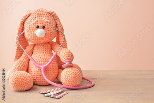 Stethoscope, pills and baby toy on table