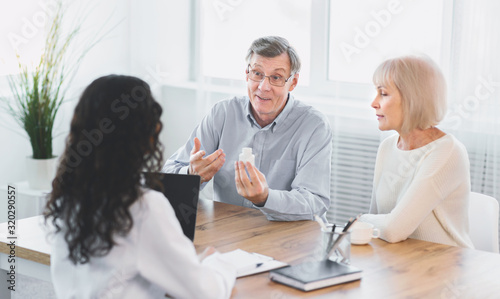Mature couple asking their doctor about pills