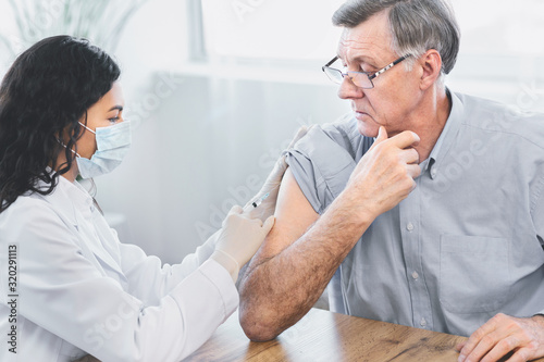 Fotomural Mexican doctor doing vaccination to elderly man
