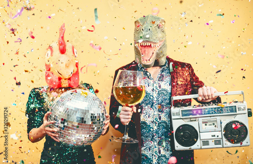 Photo Crazy couple celebrating new year eve wearing chicken and dinosaur t-rex mask -