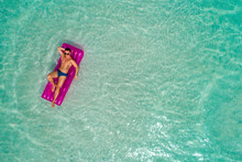 Summer Holiday Fashion Concept - Tanning Man At The Beach On A Turquoise Sea Shot From Above. Top View From Drone. Aerial View Of Slim Men Sunbathing Lying On A Beach In Thailand.