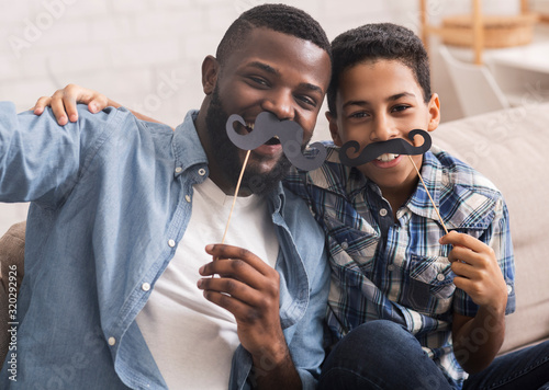 Stampa su Tela Black father and son taking selfie, holding fake moustache on sticks