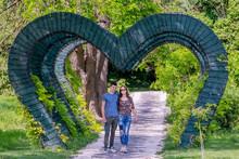 Young Engaged Couple Walk Unde...