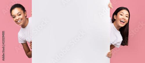 Fototapeta Two Girls Peeking Out Of Blank White Board, Pink Background obraz