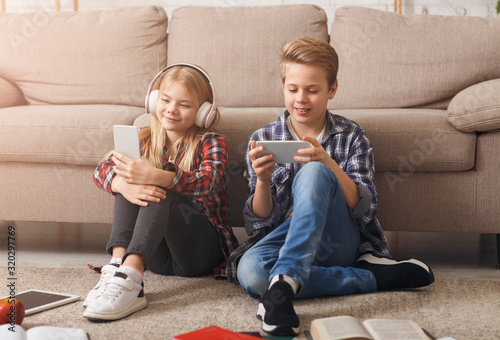 Brother And Sister Using Smartphones Sitting On Floor Indoor
