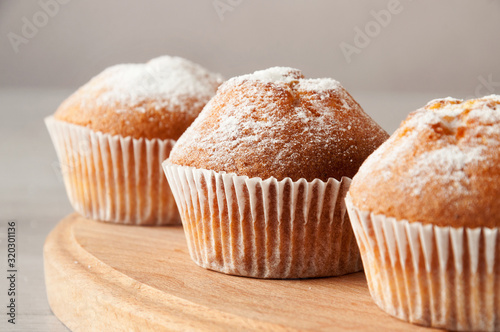 Fototapeta Tasty muffin closeup on a wooden board, selective focus.