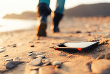The Concept Of Losing Your Phone. The Smartphone Lies On The Sand, On The Beach. In The Background, Blurred Removing Footsteps Of A Man
