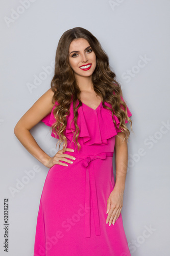 Pretty Young Woman Is Posing In Magenta Dress Wall mural