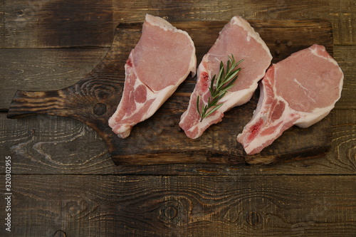 Valokuvatapetti raw pork loin or sliced of meat isolated on a wooden cutting board on a wooden rustic background