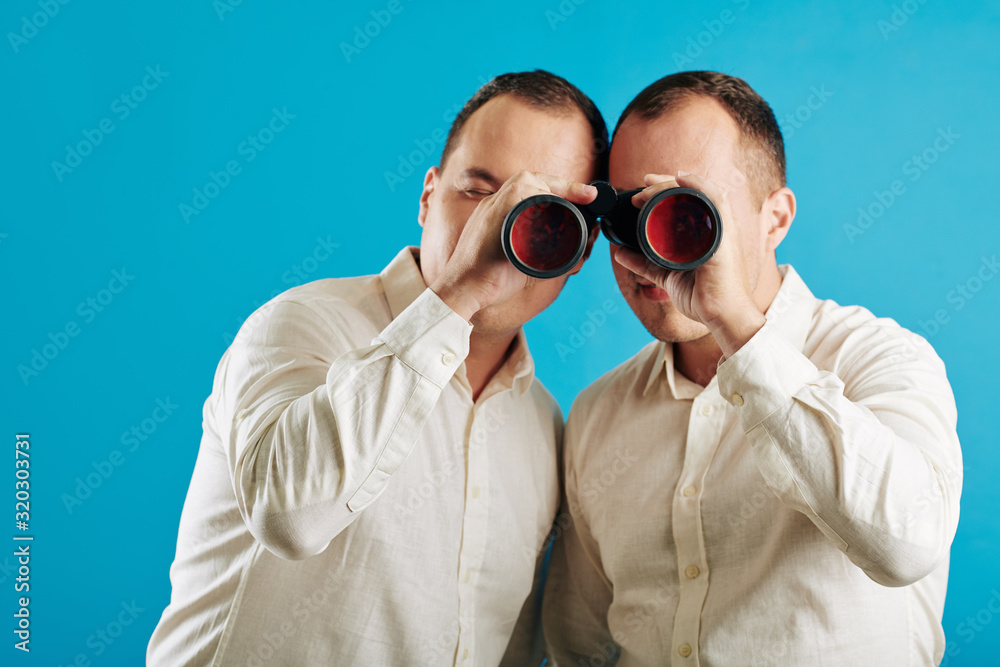 Fototapeta Unrecognizable twin brothers wearing white shirts looking through binoculars at camera, blue wall background