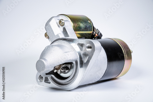 Fototapeta Starter of an internal combustion engine New Spare part for car on a gray background obraz