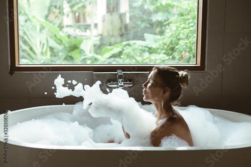 Cuadros en Lienzo Woman relaxing in foam bath with bubbles in dark bathroom by window
