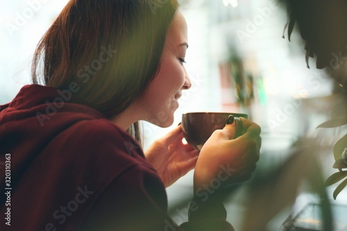 Obraz Caucasian young woman enjoying coffee drinking in cafe, close up - fototapety do salonu