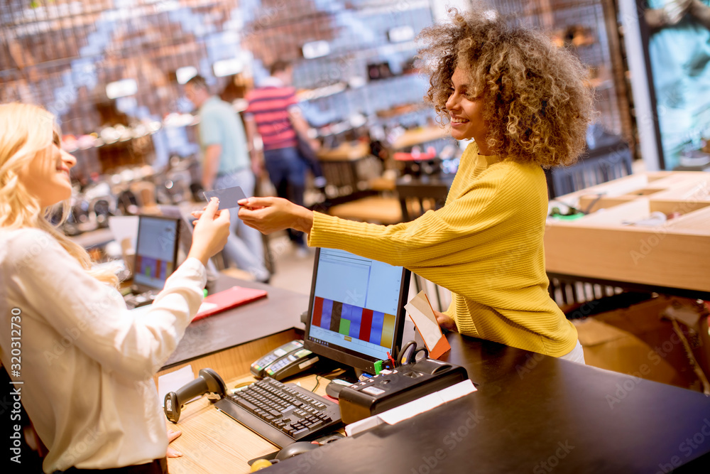 Fototapeta Happy woman customer paying with credit card in fashion showroom