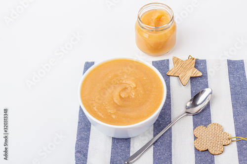 Fresh homemade applesauce in white bowl and jar with fruit puree on white table Canvas Print