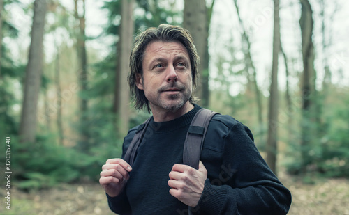 Man in black woolen sweater and backpack hiking in forest. Fototapet