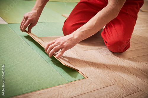 Fototapeta worker laying laminate floor covering at home renovation obraz na płótnie