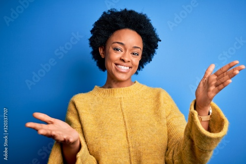 Photo Young beautiful African American afro woman with curly hair wearing yellow casual sweater smiling cheerful offering hands giving assistance and acceptance