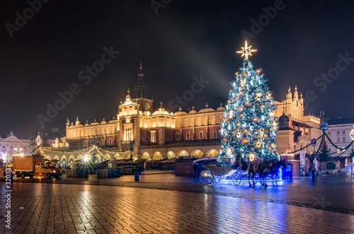 Krakow, Poland, Main Square and Cloth Hall in the winter season, during Christmas fairs decorated with Christmas tree.