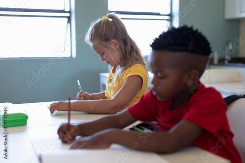 Fototapeta Schoolchildren writing during a lesson in an elementary school classroom obraz