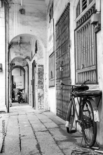 Monochromatyczne zdjęcie retro roweru w wąskiej uliczce, stare miasto