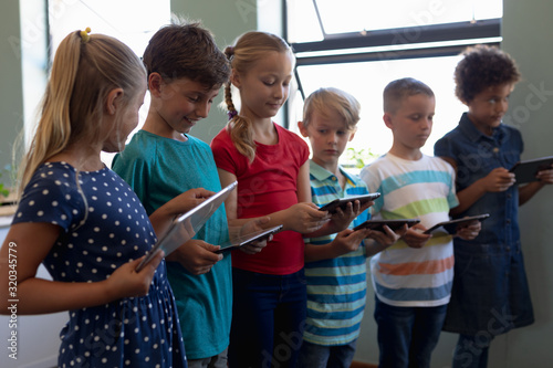 Group of schoolchildren standing in a line and using tablet computers