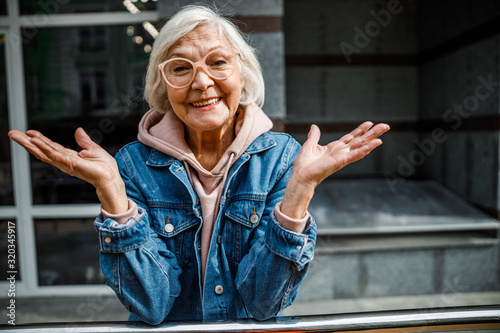 fototapeta na szkło Happy mature woman standing outdoors stock photo