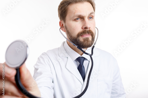 Attentive bearded doctor in white auscultating with stethoscope isolated white b Canvas Print